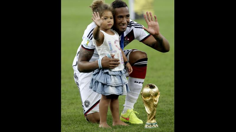 Germany's Jerome Boateng with the World Cup trophy and his daughter following their 1-0 victory over Argentina in the World Cup final in Rio de Janeiro in 2014. AP Photo