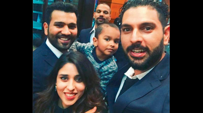 Yuvraj Singh with Rohit Sharma (carrying Shikhar Dhawan's son Zoravar) and his wife Ritika in England. DC File Photo