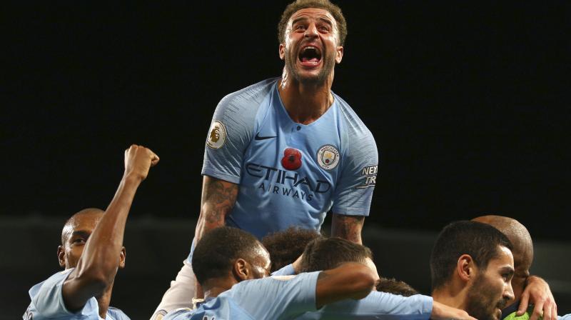 Manchester City's Kyle Walker climbs atop his teammates to celebrate a goal scored by Ilkay Gundogan. AP Photo