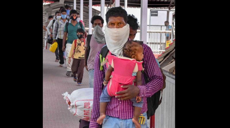 A migrant carrying his child arrives to board a local passenger train at Danapur railway station to reach his destination. (PTI)