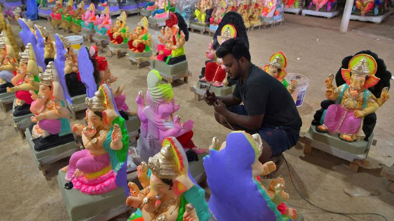 An artisan paints to give finishing touches to a clay idol of Ganesha ahead of the Ganesh Chaturthi festival in Bangalore on September 4, 2021. (Manjunath Kiran / AFP)
