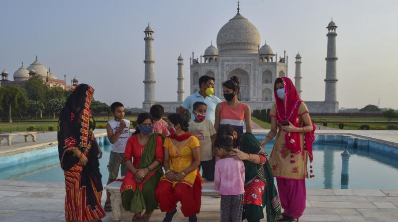 A group of Indians who visited the Taj Mahal monument that was Wednesday reopened to public after the lockdown to curb the spread of coronavirus gather to get photographed in Agra. (Photo: PTI)