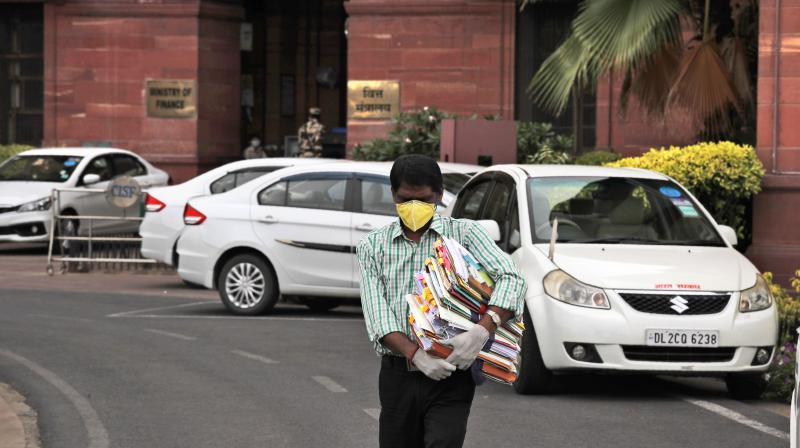An Indian Finance Ministry employee walks carrying files outside the ministry building on April 20, 2020. An increasing number of officers are opting to work from home amid concerns over the coronavirus epidemic in New Delhi. (AP)