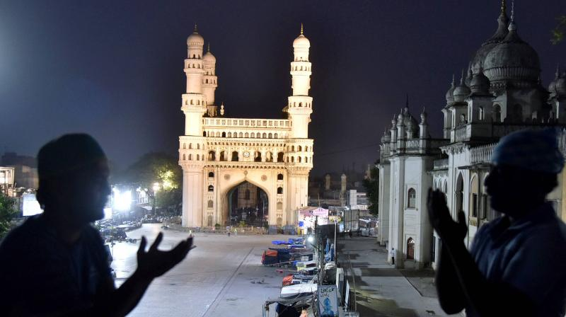 Two men pray with Hyderabad's iconic monument Charminar in the background on Friday night, April 24, 2020 even as the Union Home Minister sounded an alarm on the coronavirus situation in the city. (PTI)