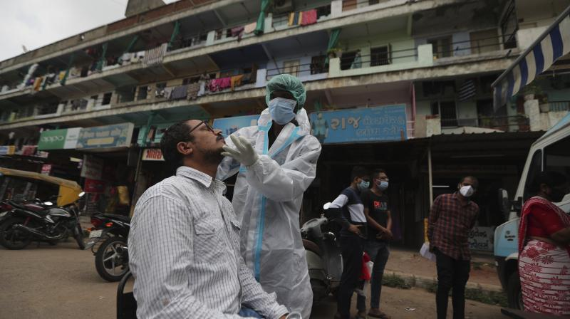 A health worker takes a swab sample of a person for COVID-19 test in Ahmedabad. AP Photo