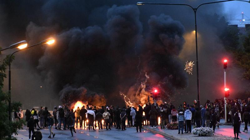 Smoke billows from burning tyres and pallets and fireworks as a few hundred protesters riot in the Rosengard neighbourhood of Malmo, Sweden. (AP)