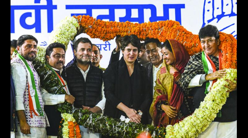 Congress leaders Rahul Gandhi and Priyanka Gandhi being garlanded during an election campaign at Hauz Qazi Chowk in New Delhi on Wednesday. (Photo: PTI)