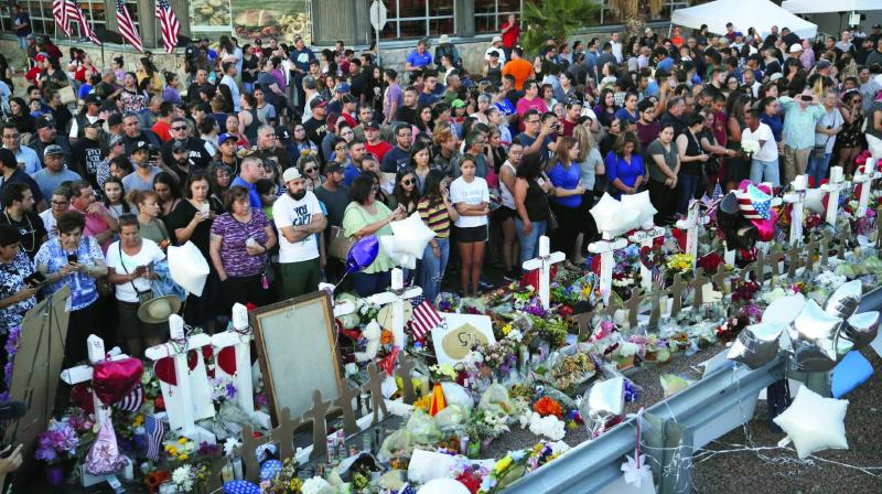 People gather around a makeshift memorial at the scene of a mass shooting at a shopping complex in El Paso, Texas, on Tuesday. (Photo: AP)