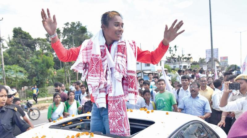 Hima Das waves after arriving in Guwahati on Friday. (Photo: AFP)