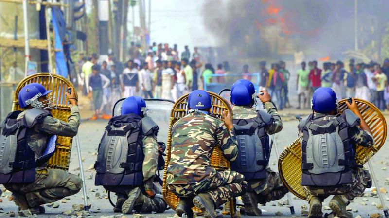 Police jawans try to protect themselves as protesters throw stones on them during an agitation against the Citizenship Amendment Bill (CAB) at Santragachi in Howrah district of West Bengal on Saturday. (Photo: PTI)