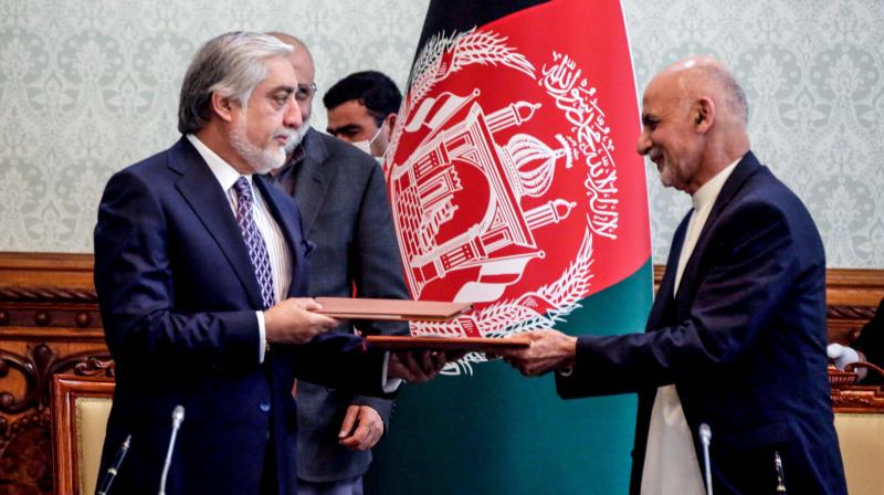 In this handout photograph taken on May 17, 2020 and released by Afghanistan's Office of Chief Executive, Afghan President Ashraf Ghani (R) and his rival Abdullah Abdullah (L) exchange documents after signing a power-sharing deal agreement at the Presidential Palace in Kabul. AFP Photo