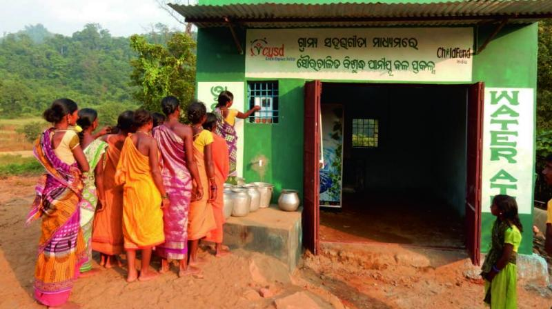 A woman collects water from an ATM in Chilipadar village.