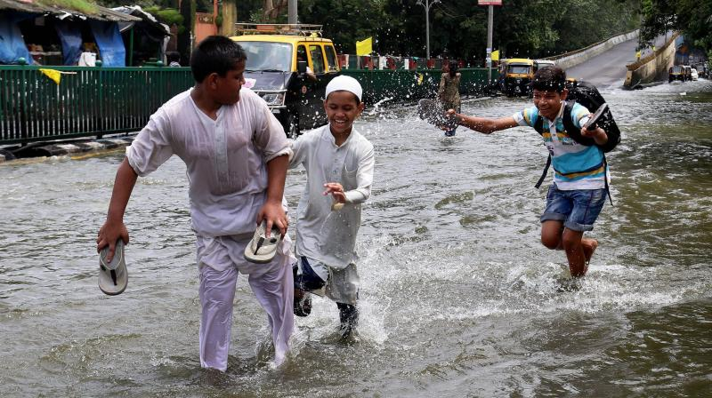 People wade at a flooded road in Thane, Mumbai on Wednesday, a day after heavy downpour. (Photo: PTI)