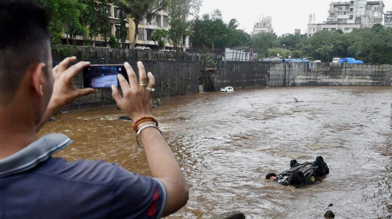 A man clicks picture of a car floating in a nullah in Mumbai on Wednesday, a day after heavy downpour. (Photo: PTI)