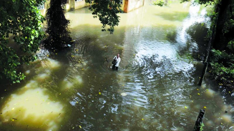 People wade through knee-deep water at Wadala BBT on Wednesday after heavy rains lashed the city. (Photo: Rajesh Jadhav)