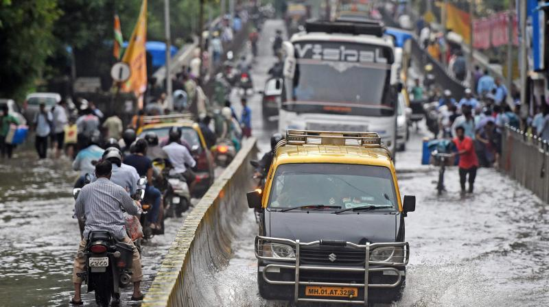 Vehicles plying at a waterlogged road after heavy rains, in Mumbai. (Photo: PTI)