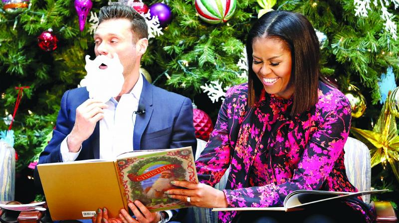 In this file photo First lady Michelle Obama with television and radio host Ryan Seacrest read Twas the Night Before Christmas during a holiday event at Children's National Health System in Washington. (Photo: AP)