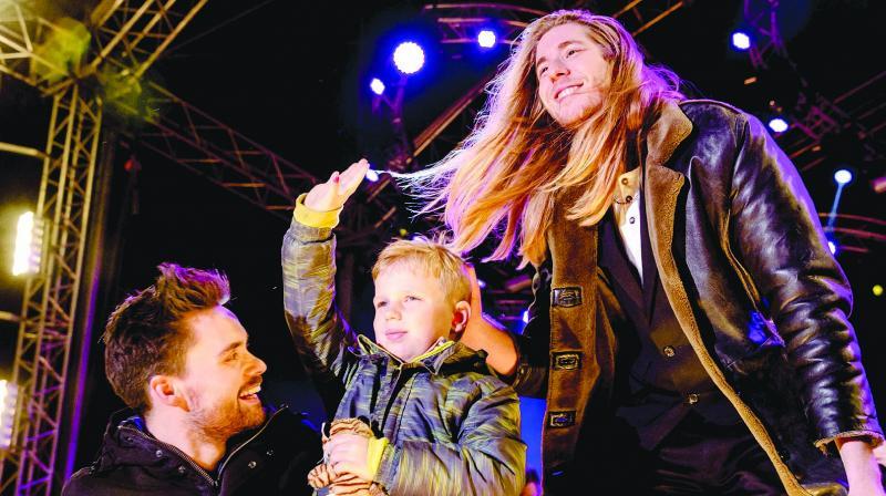 Dutch 3FM DJs Domien Verschuuren (left) and Frank van der Lende perform with 6-year-old Tijn Kolsteren. They raised $2.6 million at the House of Glass of Serious Request in Breda, Netherlands on Saturday. (Photo: AFP)