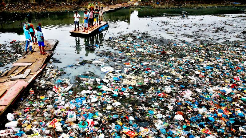 A man guides a raft through a polluted canal littered with plastic bags and other garbage in Mumbai, India. (Photo: AP)