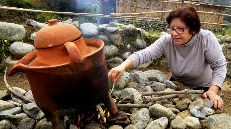 Yiannoula Lazarou tends to a fire boiling perfume inside a second millennium BC distiller discovered in Cyprus at the ancient perfume theme park and museum in Korakou, Cyprus. (Photo: AP)