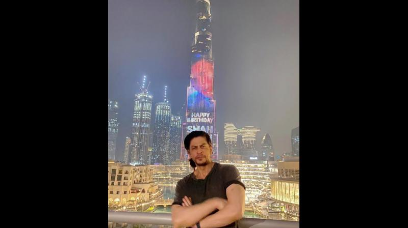 Shah Rukh standing in front of the Burj Khalifa