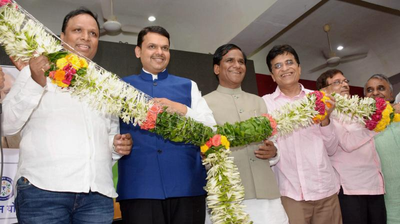 Chief Minister of Maharashtra Devendra Fadanvis and party state president Ravsaheb Danve along with Ashis Selar, Kirit Somaiya and other leaders being garlanded during celebrations after the BMC poll results at Mumbai BJP office. (Photo: PTI)