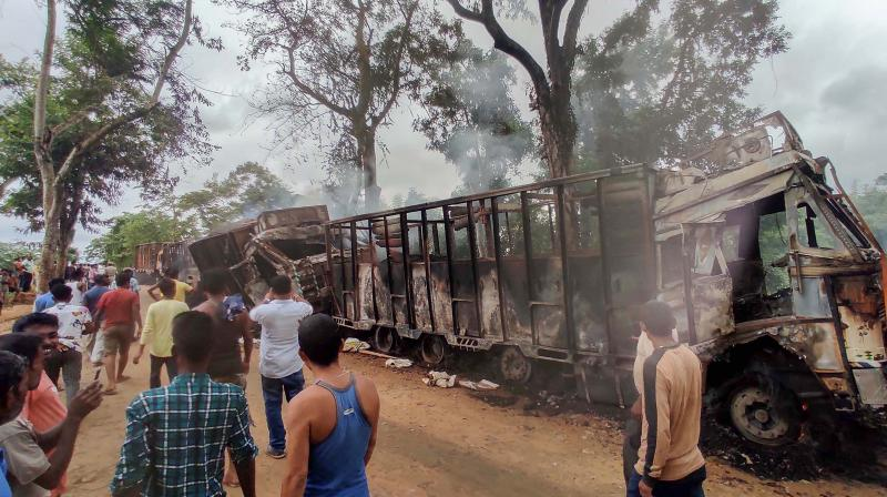 Local people look at trucks which were set on fire allegedly by members of the Dimasa National Liberation Army (DNLA) at Dayangmukh in Dima Hasao district of Assam, Friday, Aug. 27, 2021. (PTI Photo)