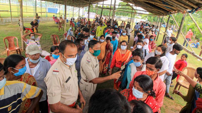 Police personnel instruct beneficiaries to maintain queues as they wait to receive COVID-19 vaccine during a mega vaccination drive camp organised by Health Unit, Bolpur Municipality at Bolpur Stadium in Birbhum district, West Bengal, Aug. 25, 2021. (PTI)