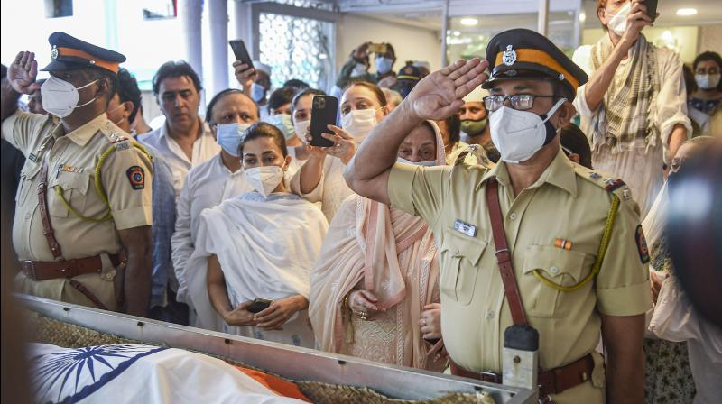 Police personnel salute during the guard of honour to Bollywood legendary actor Dilip Kumar on his funeral, in Mumbai, Wednesday, July 7, 2021. (PTI /Kunal Patil)