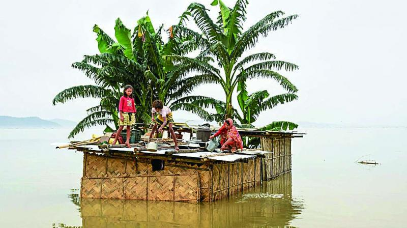 A family marooned on the top of a hut in the flood-hit locality of Panikhaiti in Kamrup district of Assam on Monday. (Photo: PTI)