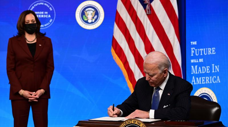 US President Joe Biden with Vice President Kamala Harris (L) signs a a 'Made in America' Executive Order, to increase the amount of federal spending that goes to American companies in the South Court Auditorium at the White House on January 25, 2021 in Washington, DC. (JIM Watson / AFP)