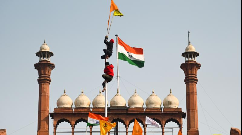 Protesters climb a flagpole at the ramparts of the Red Fort as farmers continue to demonstrate against the central government's recent agricultural reforms in New Delhi on January 26, 2021. (Sajjad HUSSAIN / AFP)
