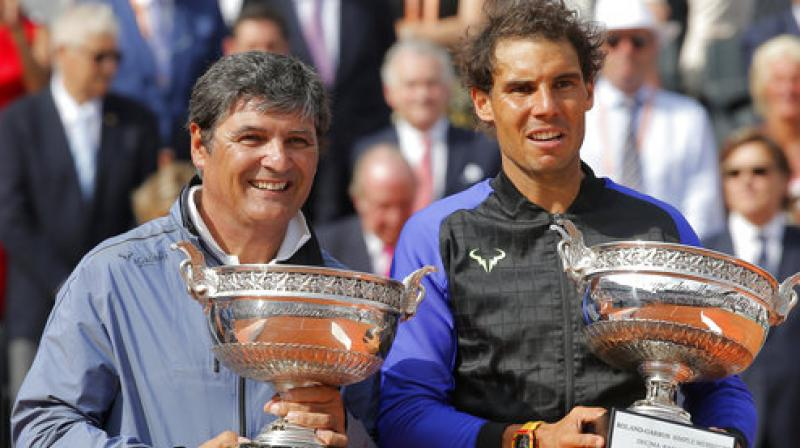 Spain's Rafael Nadal, right, poses with the special Decima cup while his uncle Toni Nadal holds the men's winner cup after the final match of the French Open. (Photo: AP)
