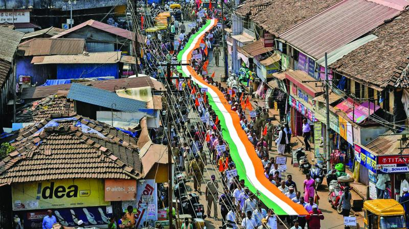 People carry a 350-foot-long Tricolour during a rally in support of the National Register of Citizens (NRC) and Citizenship Amendment Act (CAA) at Sawantwadi in Sindhudurg district  of the Konkan region on Monday. (Photo: PTI)