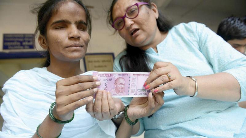 In this photograph taken on November 28, advocacy manager at the Blind People's Association (BPA), Kinnary Desai (R) shows a visually impaired woman how to identify a new Rs 2000 note at the Blind People's Association in Ahmedabad. (Photo: AFP)