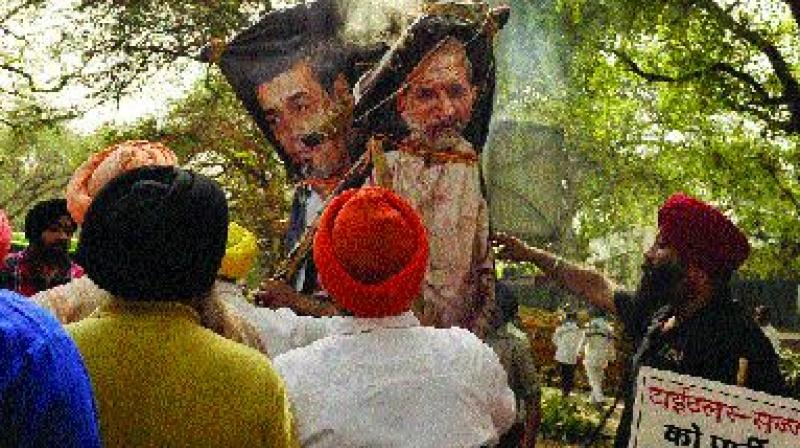 Akalis burn effigies of Sajjan Kumar and Jagdish Tytler during a protest against 1984 anti-Sikh riots outside the Congress head office in New Delhi on Tuesday. (Pritam Bandyopadhyay)