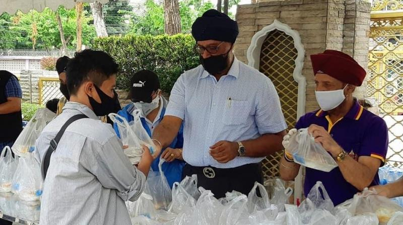Pinderpal Singh Madan, of the Sri Guru Singh Sabha, distributes packets of food (Photo: By arrangement)
