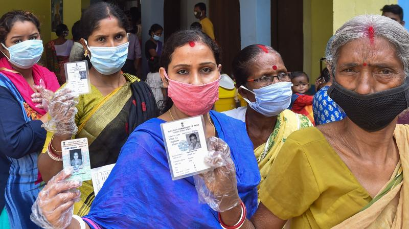 Women show their identity cards as they wait to cast votes at a polling station, during the first phase of Assembly polls, in Midnapore on Saturday. (Photo: PTI)