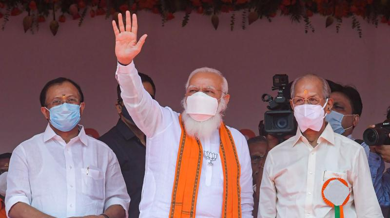 Prime Minister Narendra Modi with Union Minister of State Vellamvelly Muraleedharan and BJP candidate E Sreedharan (R) waves at the crowd during an election campaign rally for Assembly polls in Palakkad constituency. (Photo: PTI)