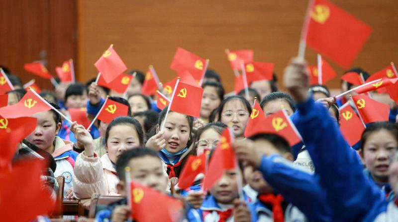 Students waving flags of the Communist Party as they prepare to watch a movie
