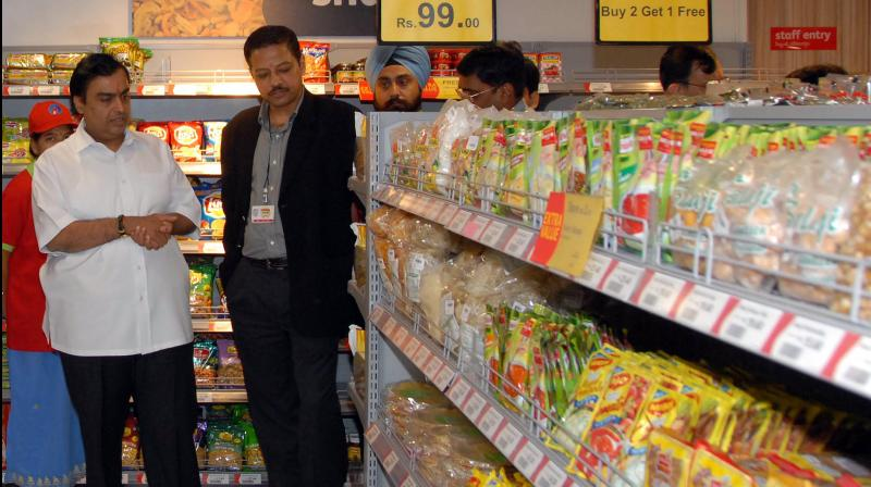Chairman of India's Reliance Industries Mukesh Ambani (L) looks at rows of produce during a visit to a Reliance Fresh supermarket in Hyderabad. (AFP Photo)