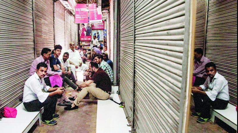 Cloth market traders sit outside their closed shops during a protest on the fourth day of the new GST regime at Chandni Chowk Market in New Delhi on Tuesday. (Photo:  PTI)
