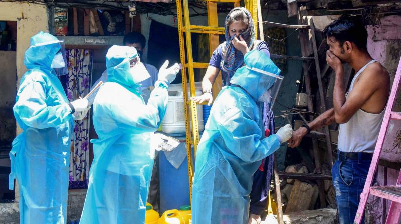 Health workers wearing protective suits screen resident of Kumbharwada during a house-to-house health survey, after detection of some COVID-19 positive cases, during the nationwide lockdown, at Dharavi in Mumbai. PTI photo