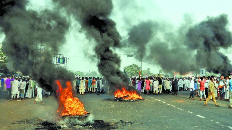 Protesters from the Muslim community burn tyres during a demonstration against National Register of Citizens and Citizenship (Amendment) Bill in Howrah district of West Bengal on Friday. (Photo: PTI)