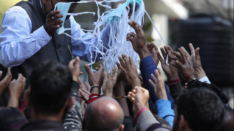 A volunteer distributes masks outside a government hospital as a precaution against COVID-19 in Jammu on March 16, 2020. (AP)