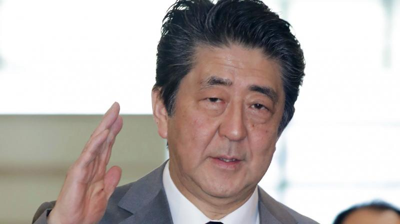 Japan's Prime Minister Shinzo Abe gestures as he arrives at his office in Tokyo on March 18, 2020. Abe said the country will expand quarantine measures and a ban on entry from parts of countries including Italy and Spain affected by the coronavirus outbreak. (AFP)