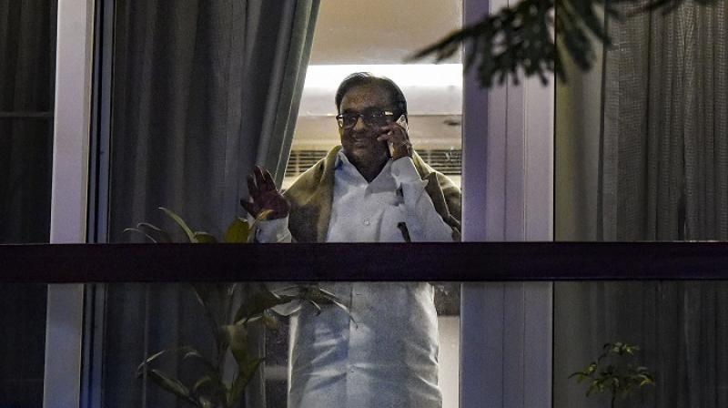 Dressed in his trademark long-sleeved white shirt and dhoti, Chidambaram was surrounded by a posse of newsmen and photographers. (Photo: PTI)