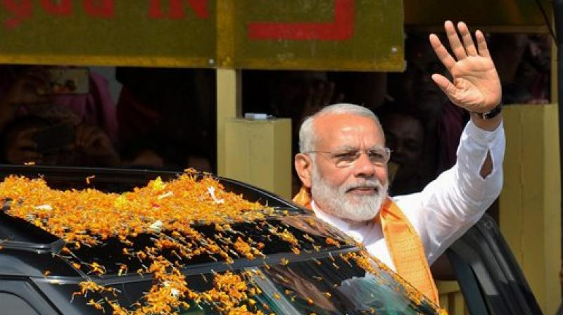 Prime minister Narendra Modi wave at people during his visit to Lord Lingaraj temple in Bhubaneswar. (Photo: AP)