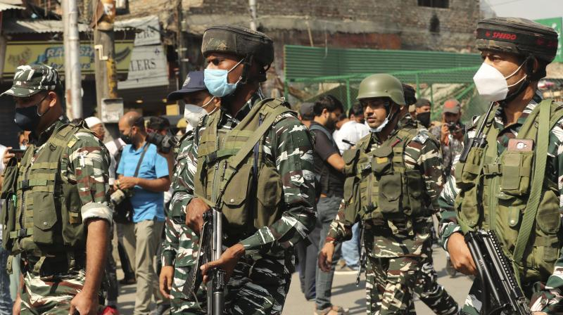 Indian paramilitary soldiers keep guard near the site of a grenade attack at a busy market in Srinagar, Tuesday, Aug. 10, 2021. (AP/Mukhtar Khan)