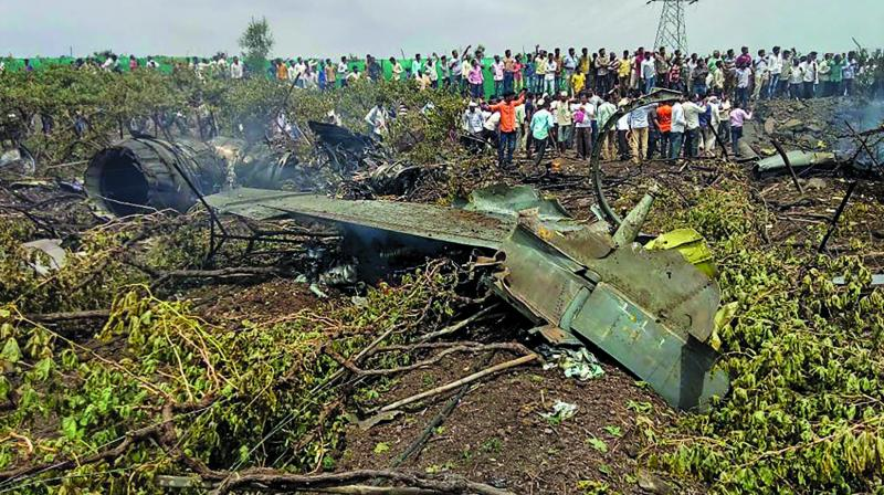 People gather around the mangled remains of a Su-30 MKI fighter jet after it crashed at Wavi-Tushi village, near Nashik. (Photo: PTI)